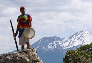 Israel Hurtado with drum and walking stick with Mt. Shasta in the background